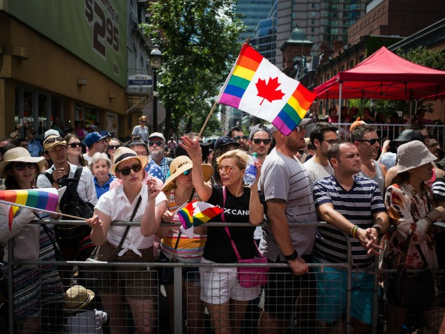 TORONTO, CANADA - JULY 3: Spectators watch along Yonge Street, at the annual Pride Festival parade, July 3, 2016 in Toronto, Ontario, Canada. Prime Minister Justin Trudeau will make history as the first Canadian PM to march in the parade. (Photo by Ian Willms/Getty Images)