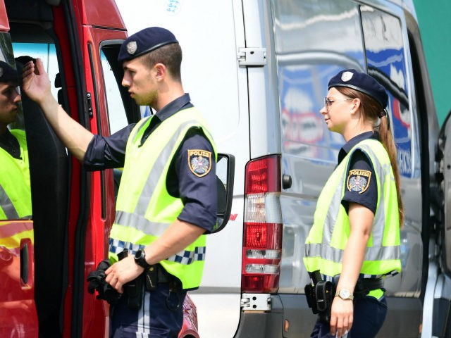 Austrian police officers search a van at the Austrian-Hungarian border of Nickeldsdorf on July 12, 2016. It's holiday season at Nickelsdorf on Austria's border with Hungary as families hit the highway but although the streams of refugees seen here a year ago have gone, things are far from normal. / …