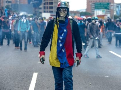 TOPSHOT - Opposition activists protest against President Nicolas Maduro, in Caracas on May 8, 2017. Venezuela's opposition mobilized Monday in fresh street protests against President Nicolas Maduro's efforts to reform the constitution in a deadly political crisis. Supporters of the opposition Democratic Unity Roundtable (MUD) gathered in eastern Caracas to …