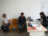BERLIN, GERMANY - MAY 03: Shelter employee Katrin Krug (R) assists resident Abdul Hakim (C) from Syria with bureaucratic paperwork as resident Mohammad Nader Mohamedi (L) from Afghanistan waits his turn in the counselling center at a shelter for refugees and migrants in Marienfelde district on May 3, 2017 in …
