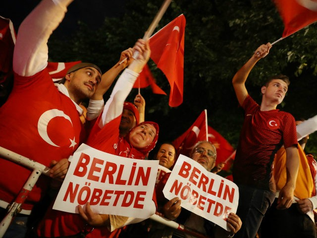 BERLIN, GERMANY - JULY 15: Pro-Erdogan Berlin Turks, including some holding signs in Turkish that read: 'Berlin Holds Watch,' wave Turkish flags during a gathering in front of the Turkish Embassy to commemorate the first anniversary of the failed coup in Turkey on July 15, 2017 in Berlin, Germany. Hundreds …
