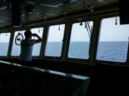 A member of the Aquarius rescue ship of the European search and rescue association 'SOS Mediterranee', uses binoculars during a search operation on the Mediterranean Sea, 20 nautical miles from the Libyan coast, on August 11, 2017. The Libyan navy on August 11, 2017, ordered foreign vessels to stay out …