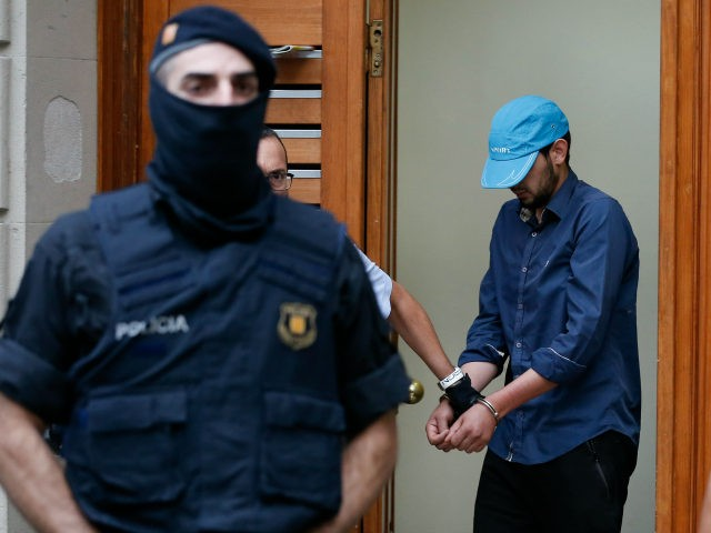 Catalan autonomous police officers, known as Mosso d'Esquadra, detain a cuffed suspect in Ripoll during a search linked to the deadly terror attacks in Barcelona and the seaside resort of Cambrils on August 18, 2017, a day after a van ploughed into the crowd, killing 14 persons and injuring over …