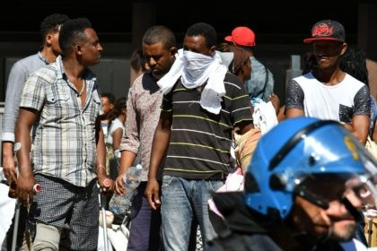 "Refugees and asylum seekers wait after being displaced from a palace in the center of Rome on August 23, 2017. The UN's refugee agency (UNHCR) voiced ""grave concern"" over the eviction of 800 people from a Rome building squatted mainly by asylum seekers and refugees from Eritrea and Ethiopia. The …"