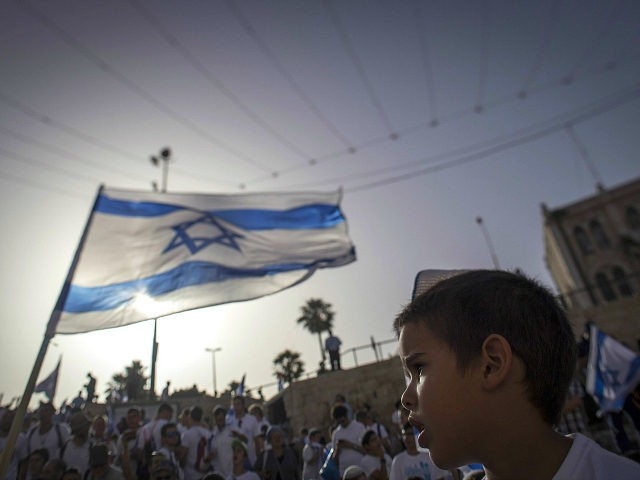 JERUSALEM, ISRAEL - JUNE 05: (EDITORS NOTE: A variable plane lens was used in the creation of this image) Thousands of young Jewish boys wave Israeli flags as they celebrate Jerusalem Day, dancing and marching their way through Damascus Gate to the Western Wallon June 5, 2016 in Jerusalem, Israel. …