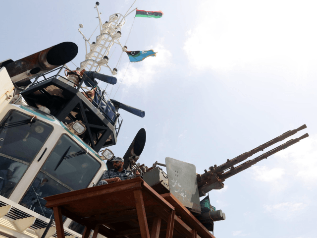 A member of the Libyan coastguards sits behind a machine gun as Mohammed Khalifa al-Guwail (unseen), the acting prime minister of Libya's disputed government, tours one of the coastguard's vessels off the coast of the eastern port city of Misrata on May 9, 2015.