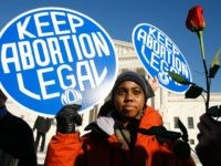 "WASHINGTON - JANUARY 22: Local pro-choice activist Lisa King holds a sign in front of the U.S. Supreme Court as a pro-life activist holds a rose nearby during the annual ""March for Life"" event January 22, 2009 in Washington, DC. The event was to mark the anniversary of the 1973 …"