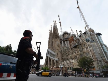 """Police officers stand guard in front of the """"Sagrada Familia"""" (Holy Family) basilica in Barcelona on August 19, 2017, two days after a van ploughed into the crowd, killing 13 persons and injuring over 100. Drivers have ploughed on August 17, 2017 into pedestrians in two quick-succession, separate attacks in …"""