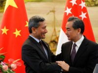 Singapore's Foreign Minister Vivian Balakrishnan, left, shakes hands with Chinese Foreign Minister Wang Yi after a joint press conference following their meeting at the Ministry of Foreign Affairs in Beijing Monday, June 12, 2017. (AP Photo/Andy Wong)