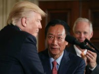 US President Donald Trump shakes hands with Terry Gou (C), Chairman of Foxconn, an electronics supplier, while Sen. Ben Johnson (R-WI) (R) stands nearby during an announcement that the company will open a manufacturing facility in Wisconsin, during an event in the East Room of the White House July 26, …