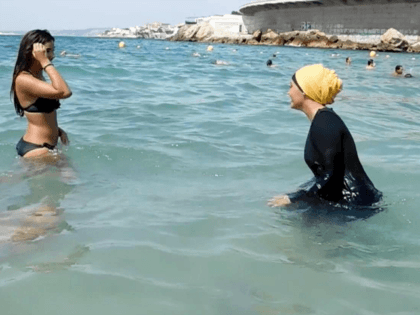 In this image taken from video, Nesrine Kenza who says she is happy to be free to wear a burkini, and two unidentified friends wade into the sea, in Marseille, France, Monday Aug. 29, 2016.