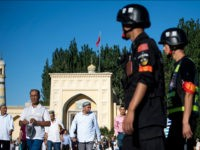 This picture taken on June 26, 2017 shows police patrolling as Muslims leave the Id Kah Mosque after the morning prayer on Eid al-Fitr in the old town of Kashgar in China's Xinjiang Uighur Autonomous Region. The increasingly strict curbs imposed on the mostly Muslim Uighur population have stifled life …