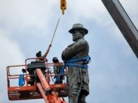 FILE- In this May 19, 2017, file photo, workers prepare to take down the statue of former Confederate general Robert E. Lee, which stands over 100 feet tall, in Lee Circle in New Orleans. Hanceville Mayor Kenneth Nail wrote to New Orleans Mayor Mitch Landrieu, asking him and city leaders to consider donating Confederate monuments recently removed from their pedestals in New Orleans to his town so they could be displayed in Veterans Memorial Park in Hanceville, Ala. Landrieu's office didn't immediately respond Monday, June 19, to an emailed request for comment. (AP Photo/Gerald Herbert, File)