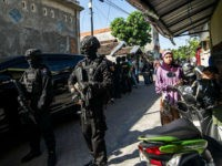 Members of the Densus 88 counter-terrorism police cordon off a road as they search a house in Surabaya, East Java province, on June 19, 2017, following the arrest of a man suspected of links with the Islamic State (IS) group. The Islamic State (IS) group claimed responsibility for the May …