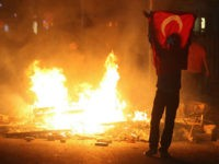 A protestor holds a national flag of Turkey during a demonstration in Ankara, early on June 3, 2013, in a nationwide wave of protests.Turkey's Islamist-rooted government faced growing pressure on June 3 after angry demonstrators clashed for a third night with police. The unrest began as a local outcry against …