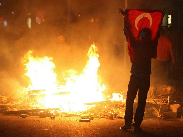 A protestor holds a national flag of Turkey during a demonstration in Ankara, early on June 3, 2013, in a nationwide wave of protests.Turkey's Islamist-rooted government faced growing pressure on June 3 after angry demonstrators clashed for a third night with police. The unrest began as a local outcry against plans to redevelop Gezi Park, a rare green spot near Taksim, but after a heavy-handed police response the protests spread to other districts -- and then to dozens of cities across Turkey. Accused by critics of pushing an increasingly conservative and authoritarian agenda, Erdogan's government is facing the biggest protests since it took power in 2002. AFP PHOTO/ADEM ALTAN (Photo credit should read ADEM ALTAN/AFP/Getty Images)