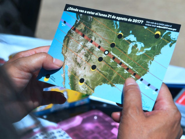 A woman views a map showing the route of the sun crossing the United States during the Solar Eclipse Festival at the California Science Center in Los Angeles, California on August 19, 2017, two days before The Solar Eclipse on Monday August 21. / AFP PHOTO / FREDERIC J. BROWN (Photo credit should read FREDERIC J. BROWN/AFP/Getty Images)