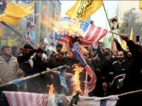 Iranians burn US flags outside the former US embassy in Tehran on November 4, 2013, during a demonstration to mark the 34th anniversary of the 1979 US embassy takeover. Thousands of Iranians shouted 'Death to America' as they demonstrated 34 years after Islamist students stormed the embassy compound in Tehran, holding 52 American diplomats hostage for 444 days. AFP PHOTO/STR (Photo credit should read -/AFP/Getty Images)