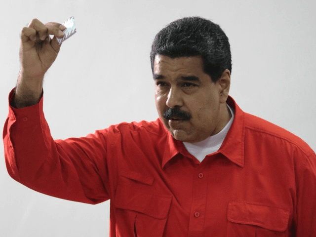 In this photo released by Miraflores Press Office, Venezuela's President Nicolas Maduro shows his ballot after casting a vote for a constitutional assembly in Caracas, Venezuela on Sunday, July 30, 2017. Maduro asked for global acceptance on Sunday as he cast an unusual pre-dawn vote for an all-powerful constitutional assembly …