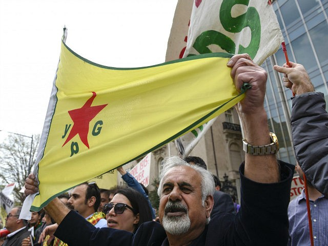 A man holds a flag of YPG, a Syria-based Kurdish militant group, during a protest against Turkish President Recep Tayyip Erdogan in front of Brookings Institution in Washington, Thursday, March 31, 2016, where President Erdogan was speaking. (AP Photo/Sait Serkan Gurbuz)