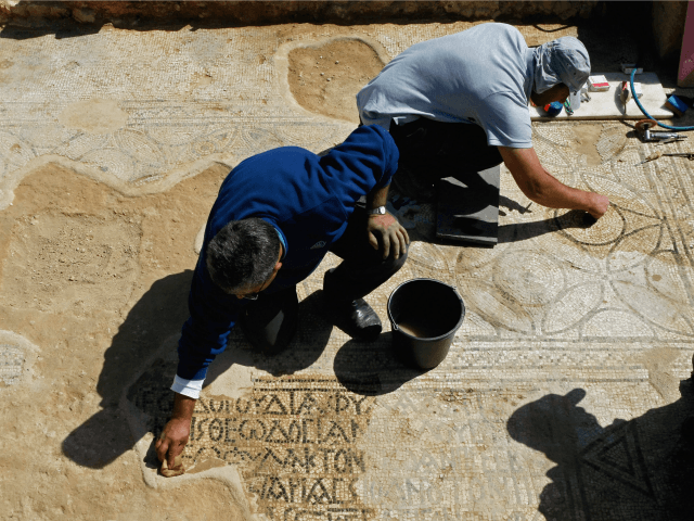 NES HARIM, ISRAEL - MARCH 12: Israeli archaeologists clean a mosaic in the ruins of a church that dates back to the Byzantine period (6th-7th century AD) which was recently unearthed during construction work, on March 12, 2009 in the community of Nes Harim near Jerusalem, Israel. The mosaic is …