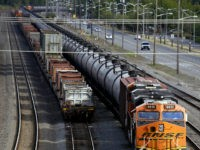 FILE - In this July 27, 2015, file photo, traffic passes one of two mile-long oil trains parked near the King County Airport in Seattle. More crude oil than ever is expected to move through Washington state, particularly since the Canadian government approved the Kinder Morgan pipeline project that will …