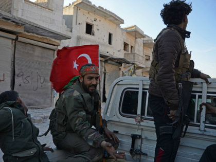 A fighter from the Turkish-backed Syrian rebels holds a Turkish flag as they sit in the back of vehicle in the northwestern border town of al-Bab on February 23, 2017 after they fully captured the town from the Islamic State (IS) group. Al-Bab, just 25 kilometres (15 miles) south of …