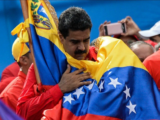Venezuelan President Nicolas Maduro holds a national flag during the closing of the campaign to elect a Constituent Assembly that would rewrite the constitution, in Caracas on July 27, 2017 on the second day of a 48-hour general strike called by the opposition. Venezuela's opposition called for a nationwide protest on Friday in outright defiance of a new government ban on demonstrations ahead of a controversial weekend election. 'The regime declared we can't demonstrate... We will respond with the TAKING OF VENEZUELA tomorrow,' the opposition coalition, the Democratic Unity Roundtable, said Thursday on its Twitter account. / AFP PHOTO / Federico PARRA (Photo credit should read FEDERICO PARRA/AFP/Getty Images)