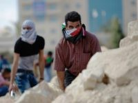 In this Tuesday, Sept. 29, 2015 file photo, Palestinian demonstrators take cover during clashes with Israeli troops near Ramallah, West Bank. Palestinian demonstrators clashed with Israeli troops across the West Bank on Tuesday as tensions remained high following days of violence at Jerusalem's most sensitive holy site, revered by Jews …