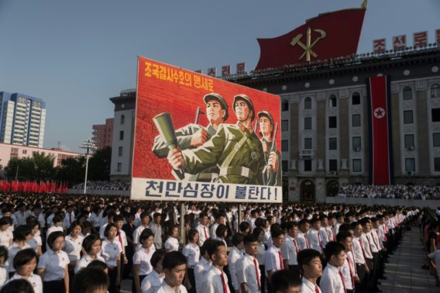 North Koreans wave banners and shout slogans at a state organised anti-American rally in Pyongyang