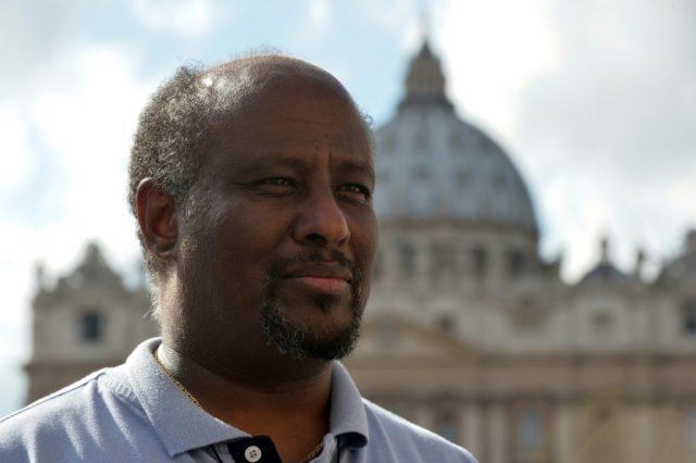Eritrean priest Mussie Zerai poses in front of Saint Peter's basilica on October 4, 2015 in Vatican