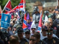 """Members of the Ku Klux Klan and others arrive for a rally July 8, 2017, calling for the protection of Southern Confederate monuments, in Charlottesville, Virginia, just a month before the August 11, 2017 """"Unite the Right"""" rally in the same city"""
