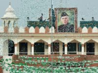 The portrait of Muhammad Ali Jinnah is seen at  the India-Pakistan Wagah border post as a Pakistani Ranger (top) unfurls the national flag on Independence Day