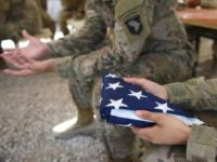 A U.S. soldier holds a flag in Afghanistan.