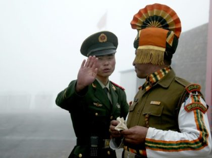 Photo taken on July 10, 2008 shows a Chinese soldier (L) gesturing next to an Indian soldier at the Nathu La border crossing between India and China in India's northeastern Sikkim state