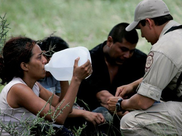 Border Patrol BORSTAR agent administers basic medical attention to illegal immigrants abandoned near Falfurrias, Texas. (AP Photo/Eric Gay)