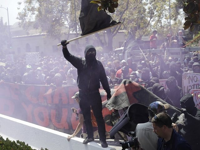 "An anti-fascist demonstrator jumps over a barricade during a free speech rally Sunday, Aug. 27, 2017, in Berkeley, Calif. Several thousand people converged in Berkeley Sunday for a ""Rally Against Hate"" in response to a planned right-wing protest that raised concerns of violence and triggered a massive police presence. Several people were arrested for violating rules against covering their faces or carrying items banned by authorities. (AP Photo/Marcio Jose Sanchez)"