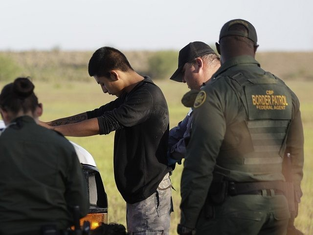 In this Aug. 11, 2017, photo, immigrants suspected of crossing into the United States illegally along the Rio Grande near Granjeno, Texas, are held by U.S. Customs and Border Patrol agents. After hitting a 17-year low shortly after President Donald Trump took office, the numbers of people coming over the border have risen four months in a row. (AP Photo/Eric Gay)