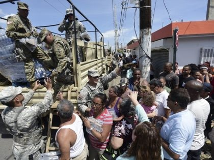 National Guardsmen arrive at Barrio Obrero in Santurce to distribute water and food among those affected by the passage of Hurricane Maria, in San Juan, Puerto Rico, Sunday, Sept. 24, 2017. Puerto Rico's nonvoting representative in the U.S. Congress said Sunday that Hurricane Maria's destruction has set the island back …
