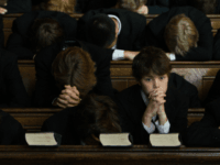 Pupils of Eton College bow their heads in prayer during the daily service in College Chapel at the iconic English private school, Eton College. Eton College was founded in 1440 by King Henry VI. The College originally had 70 King's Scholars or 'Collegers' who lived in the College and were …