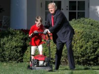 Frank Giaccio, 11, of Falls Church, Va., left, is encouraged by President Donald Trump, Friday, Sept. 15, 2017, while he mowed the lawn in the Rose Garden at the White House in Washington. The 11-year-old, who wrote the president requesting to mow the lawn at the White House, was so focused on the job at hand the he didn't notice the president until he was right next to him. (AP Photo/Jacquelyn Martin)