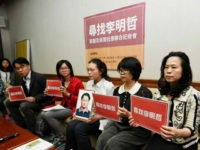 Lee Ching-yu, third from right, holds a photo of her missing husband and pro-democracy activist Lee Ming-che on March 24, 2017, during a news conference in Taipei, Taiwan, with representatives of nongovernmental organizations. (AP)