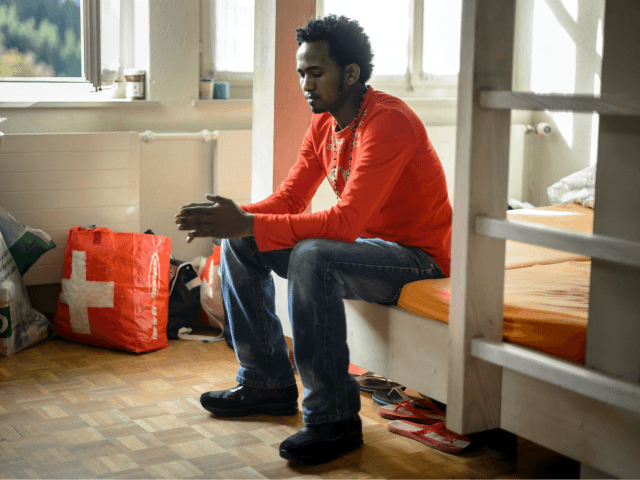 TO GO WITH AFP STORY BY NINA LARSON An Eritrean asylum seeker sits in a dormitory at the Einsiedeln Abbey in the canton of Schwyz on October 15, 2014. Thirty Eritrean asylum seekers have been given refuge at Switzerland's most famous monastery. Founded in 934 and according to legend miraculously …