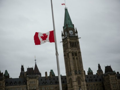 OTTAWA, ON - OCTOBER 23: A flag next to the Canadian Parliament Building is flown at half staff one day after Cpl. Nathan Cirillo of the Canadian Army Reserves was killed while standing guard in front of the National War Memorial by a lone gunman, on October 23, 2014 in …