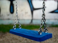 An empty swing is pictured at a Berlin playground on June 23, 2016. Is it possible to regret becoming a mother? The question first posed by an Israeli researcher has stirred a debate in Germany like in no other country, shattering a long-held taboo. / AFP / John MACDOUGALL / …