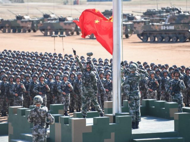 The Chinese flag is raised during a military parade at the Zhurihe training base in China's northern Inner Mongolia region on July 30, 2017. China held a parade of its armed forces on July 30 to mark the 90th anniversary of the People's Liberation Army (PLA) in a display of …