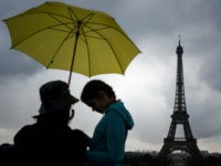 Tourists walk with umbrellas at Trocadero near the Eiffel Tower as it rains in Paris on August 10, 2017. / AFP PHOTO / PHILIPPE LOPEZ (Photo credit should read PHILIPPE LOPEZ/AFP/Getty Images)