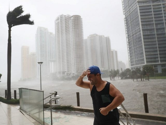 A person battles high winds and rain after taking pictures of the flooding along the Miami River as Hurricane Irma passes through on September 10, 2017 in Miami, Florida. Hurricane Irma made landfall in the Florida Keys as a Category 4 storm on Sunday, lashing the state with 130 mph …