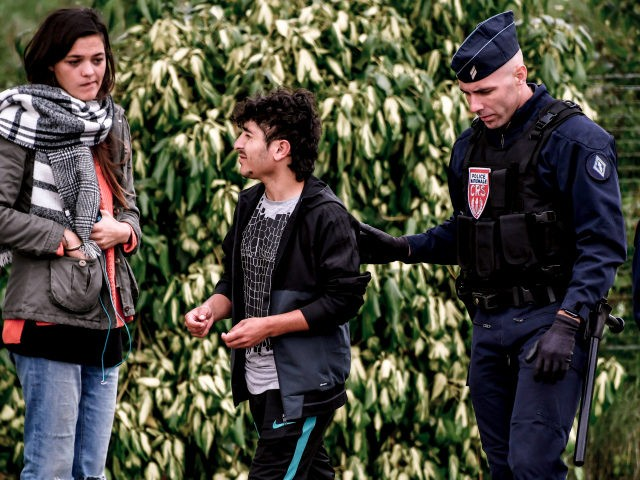 A French riot police officer arrests a migrant during a police operation to evacuate 400 Iraqi Kurds migrants who live in a makeshift camp in Grande-Synthe, northern France, on September 19, 2017. / AFP PHOTO / PHILIPPE HUGUEN (Photo credit should read PHILIPPE HUGUEN/AFP/Getty Images)