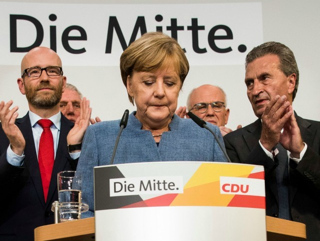German Chancellor and CDU party leader Angela Merkel (C) addresses supporters after exit poll results were broadcasted on public television at an election night event at the party's headquarters in Berlin during the general election on September 24, 2017. Germany voted in a general election expected to hand Chancellor Angela …